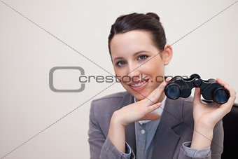 Portrait of business woman with binoculars smiling