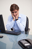 Young worried business man sitting at office desk