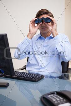 Business man looking through binoculars