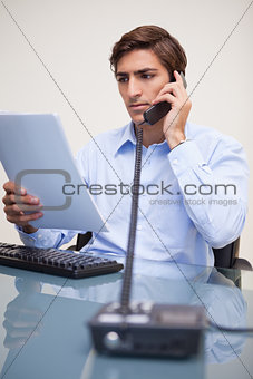 Business man looking at document while on call
