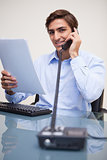 Business man holding document while on call