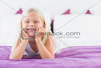 Little girl lying on a double bed
