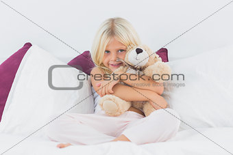 Little girl embracing her teddy bear