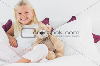 Little girl sitting near to her teddy bear