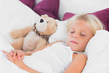 Cute girl sleeping near to her teddy bear