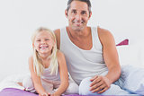 Father and his daughter sitting on a bed