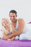Smiling father and his daughter sitting on a bed