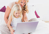 Mother and her daughter watching a laptop screen