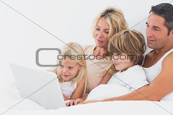 Family watching a laptop screen on a bed