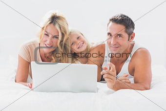 Family lying on a bed with laptop