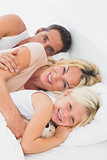 Family embracing together on a bed