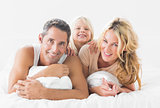 Family posing lying on a bed
