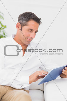 Calm man using his tablet pc