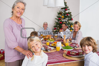 Grandmother and granddaughter standing beside the dinner table