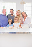 Smiling family posing in the kitchen