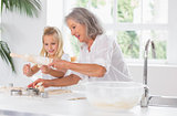 Grandmother and granddaughter using a rolling pin