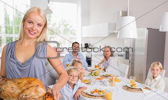 Blonde woman showing the roast turkey