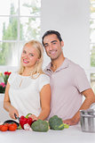 Smiling blonde woman cooking with her husband