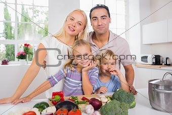 Posing family cutting vegetables