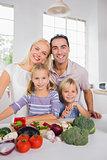 Happy posing family preparing a dinner