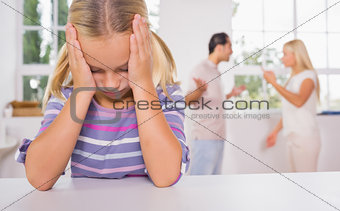 Little girl looking depressed in front of fighting parents