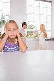 Girl looking despressed in front of fighting parents