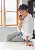 Woman sitting on worktop on the phone