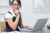 Confident female executive with laptop at desk