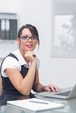 Young female executive with laptop at office desk