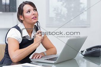 Thoughtful female executive with laptop at desk