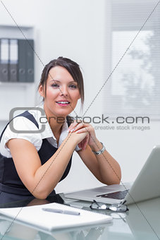 Smiling female executive sitting with laptop at desk