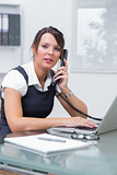 Female executive with laptop using landline phone at office