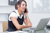 Female executive on call in front of laptop at desk