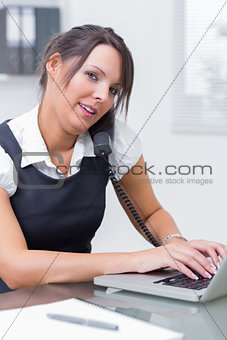 Business woman using landline phone and laptop at desk