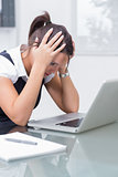 Business woman with head in hands in front of laptop at desk