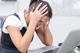 Frustrated business woman with head in hands in front of laptop at desk