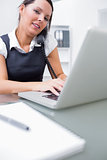 Business woman using landline phone and laptop