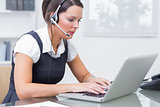 Business woman wearing headset and using laptop in office