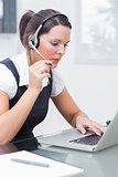 Business woman wearing headset and using laptop at desk