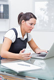 Female executive using laptop as she holds coffee cup at desk