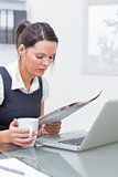 Business woman with coffee cup and laptop reading paper at office
