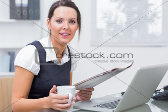 Portrait of executive with coffee and laptop reading paper at office