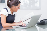 Business woman reading paper while using laptop at office