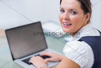 Portrait of business woman using laptop at desk