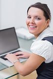 Portrait of smiling business woman using laptop at desk