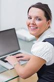 Portrait of smiling business woman using laptop at desk