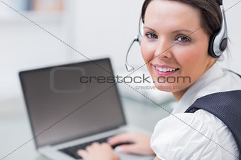 Portrait of business woman wearing headset and using laptop