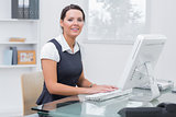 Portrait of confident female executive using computer