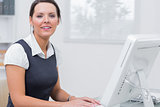 Confident female executive using computer at office