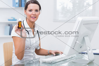 Portrait of female doctor holding medicine bottle in front of computer